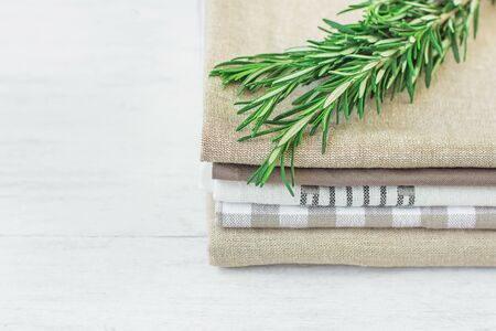 Stack of Linen and Cotton Kitchen Towels Napkins Fresh Rosemary Twig on White Wood Table
