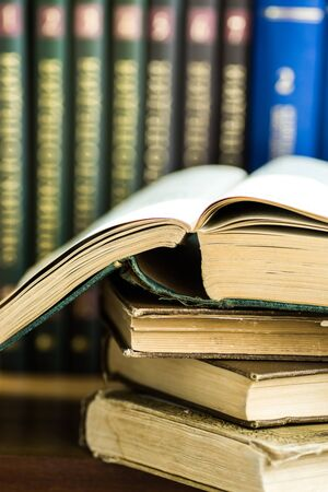 Pile of used old opened books, volumes with impressed cover in the background, university education, reading concept, close up Stockfoto