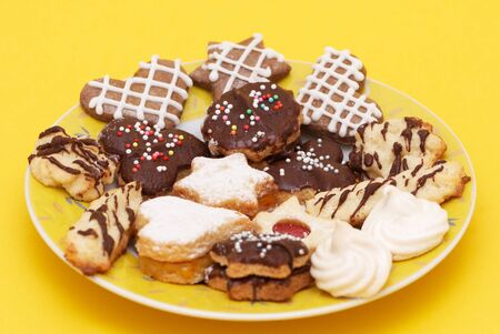 A group of Christmas cakes on yellow plate and yellow background photo