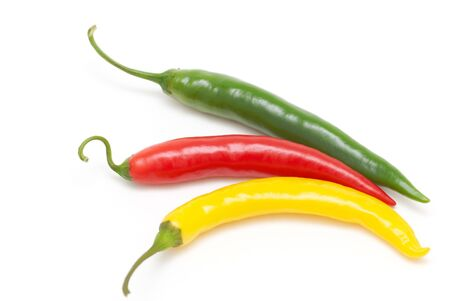 Coloured chili peppers on a white background