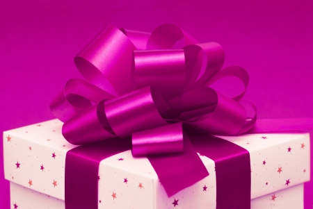 White christmas gift box with purple ribbon on pink background photo