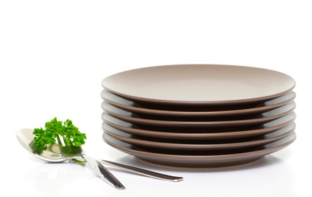 Stack of brown round plates with fork, spoon and parsley (with sample text)