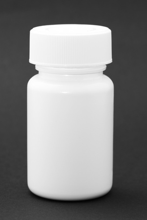 vitamins pills: White medicine bottle on black background
