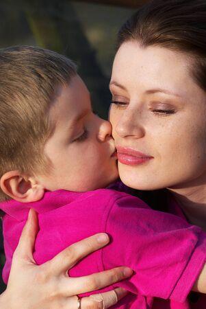 Closeup portrait of a preschool boy kissing his mother