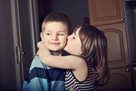 nene y nena: Adorable niña besando a un chico Foto de archivo