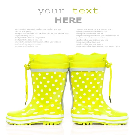 wellie: Yellow rubber boots for kids isolated on white background  with sample text