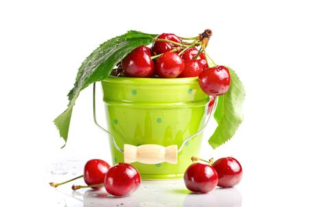 Fresh cherries with green leaves and drops in green bucket isolated on white  photo