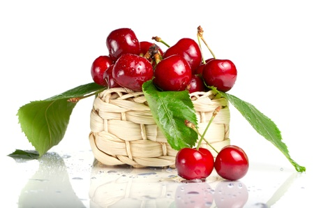 Fresh cherry berries with green leaves and drops in a basket isolated on white