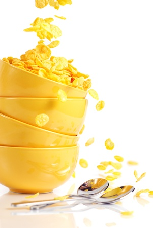Stack of yellow bowls and golden cornflakes falls into the bowl photo
