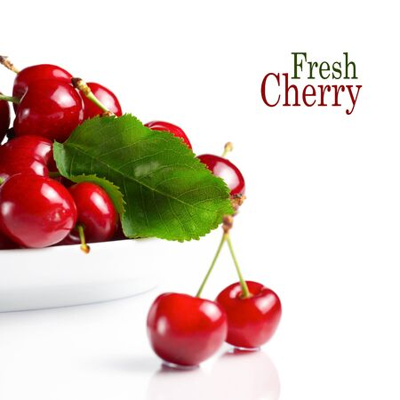 Fresh cherry berries with green leave isolated on white photo