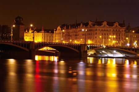 View of Prague at night through the Vltava river