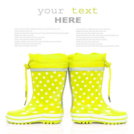 wellie: Yellow rubber boots for kids isolated on white background (with sample text)
