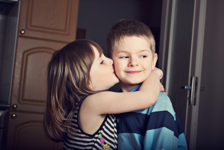 Adorable little girl kissing a boy photo