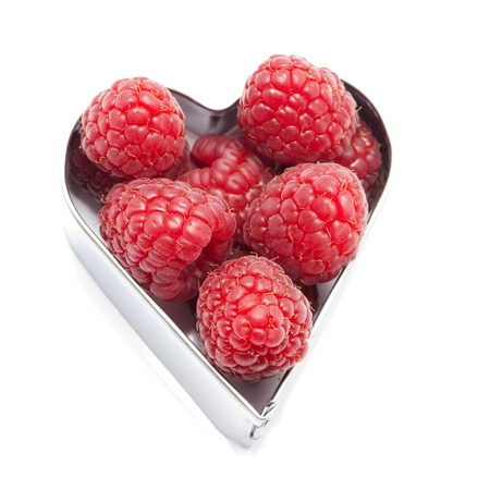 Fresh raspberries in a heart isolated on white Stock Photo - 17983669