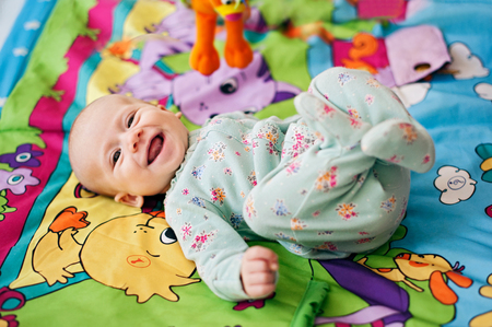 Happy little baby smiling laying in bed Stock Photo