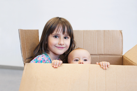 Sisters playing in a carton box Stock Photo
