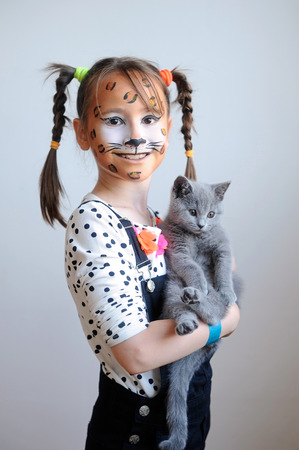 Sweet portrait of a cute little girl with face painted like a leopard holding a gray kitten Stock Photo