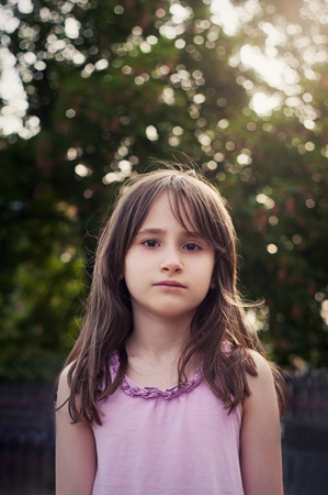 gir: Portrait of sad little gir in the summer on a green background Stock Photo
