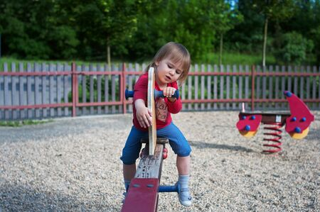 teeter: Little girl playing on a teeter on the playground Stock Photo