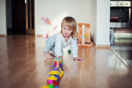Little girl playing with train. Toddler kid play with trains and cars. Educational toys for preschool and kindergarten child. Girl build toy railroad at home or daycare. Stock Photo