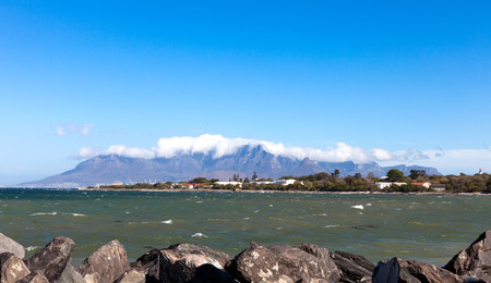 robben island: View of Table Mountain, South Africa, with the top hidden by clouds  Taken from Robben Island on a beautiful sunny day