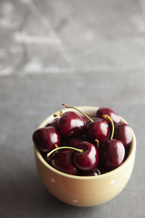 side lighting: Cherries in a green bowl on a slate worktop, taken with natural side lighting. Stock Photo