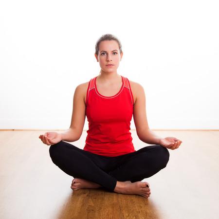 cross legged: Woman sitting cross legged doing a yoga pose in the studio, with open eyes Stock Photo