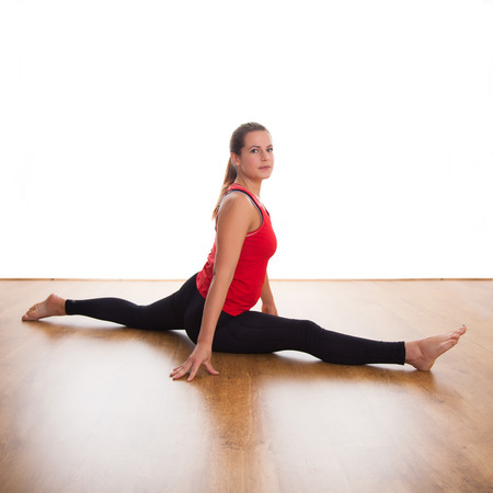 splits: Young woman exercising - stretching, legs doing the splits