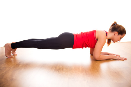 woman barefoot: Young woman exercising - doing a plank in a studio