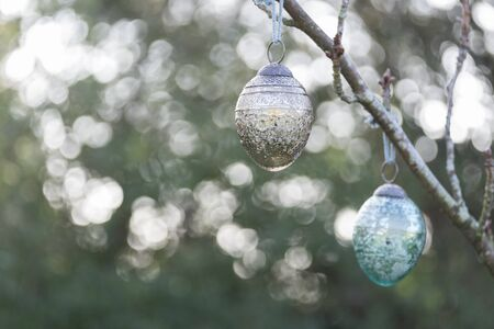back lighting: Christmas glass decoration haning outside on the branch of a tree. Back lighting has caused a bokeh effect behind the bauble.