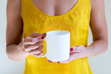 Coffee mug mockup. Female Hand holding a white coffee cup on a yellow vest background. Mock up, perfect for putting your design on.