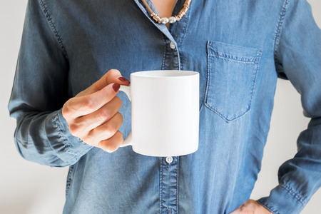 Coffee mug mockup. Female Hand holding a white coffee cup on a blue denim shirt background. Mock up, perfect for putting your design on.