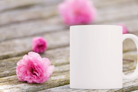 White blank coffee mug mock up,on a wooden garden table, next to blossom, add custom design or quote on to the mug. Stock Photo
