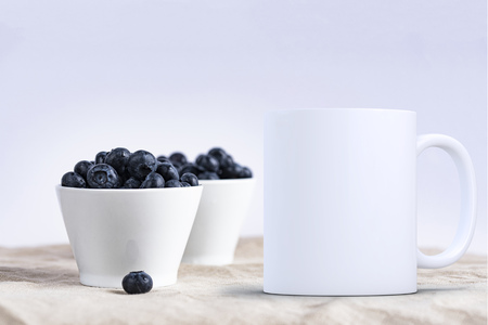 White blank coffee mug mock up, in front of two bowls of blueberries, add custom design or quote on to the mug.