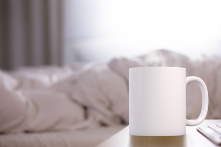 White blank coffee mug mock up, in a bedroom in front of a bed with a rumpled duvet on, add custom design or quote on to the mug.