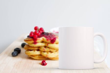 White blank coffee mug mock up, in front of a stack of pancakes with fruit on, add custom design or quote on to the mug.