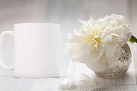 White blank coffee mug mock up, next to a small vase with one white peony, add custom design or quote on to the mug.