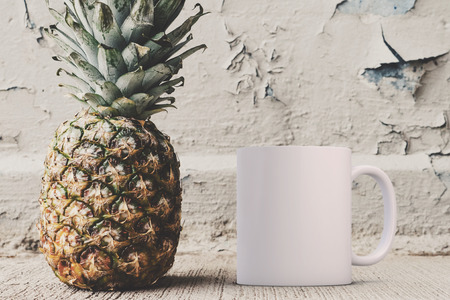 White blank coffee mug mock up, next to a pineapple, add custom design or quote on to the mug.