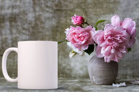 White blank coffee mug mock up, next to a vase of pink roses, add custom design or quote on to the mug.