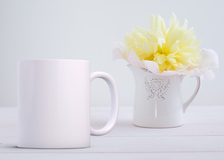 White blank coffee mug mock up, next to a small white jug with one white peony, add custom design or quote on to the mug.