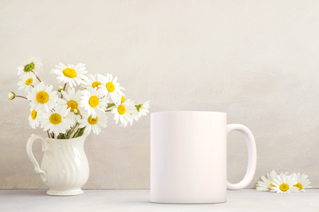 White blank coffee mug mock up, next to a vase with daisies in, add custom design or quote on to the mug. Stock Photo