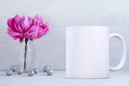 White blank coffee mug mock up, next to a vase with one peony in, add custom design or quote on to the mug.