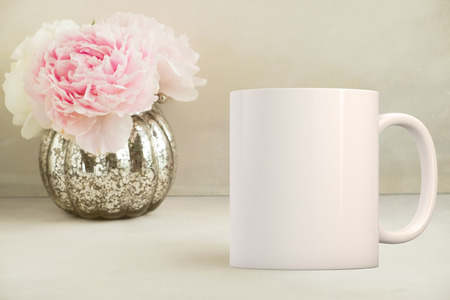 White blank coffee mug mock up, next to a vase with peonies in, add custom design or quote on to the mug.