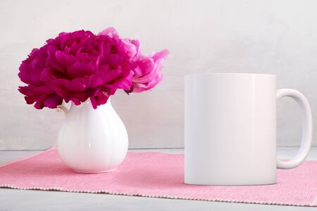 customizable: White blank coffee mug mock up, next to jug with peonies in, add custom design or quote on to the mug. Stock Photo
