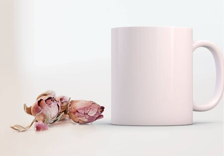 White blank coffee mug mock up, next to pretty pink rosebuds, add custom design or quote on to the mug.