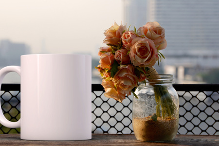 White blank coffee mug mock up, next to a vase of roses, add custom design or quote on to the mug. Stock Photo