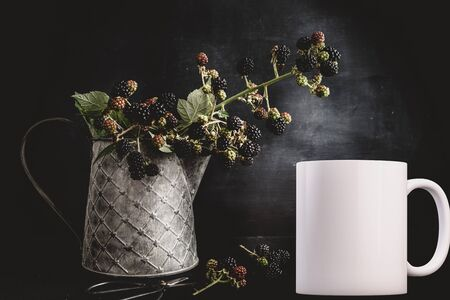White blank coffee mug mock up, next to a tin jug with a wild blackberry branch in, add custom design or quote on to the mug.