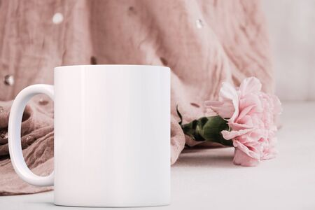 White blank coffee mug mock up, in front of a carnation, add custom design or quote on to the mug.