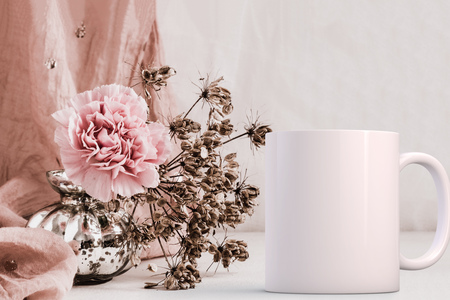 White blank coffee mug mock up, next to a vase with a carnation in, add custom design or quote on to the mug.