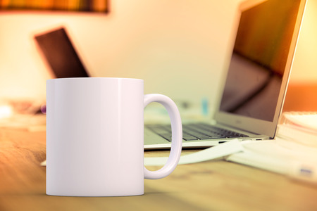 White blank coffee mug mock up, on a desk next to a laptop, add custom design or quote on to mug